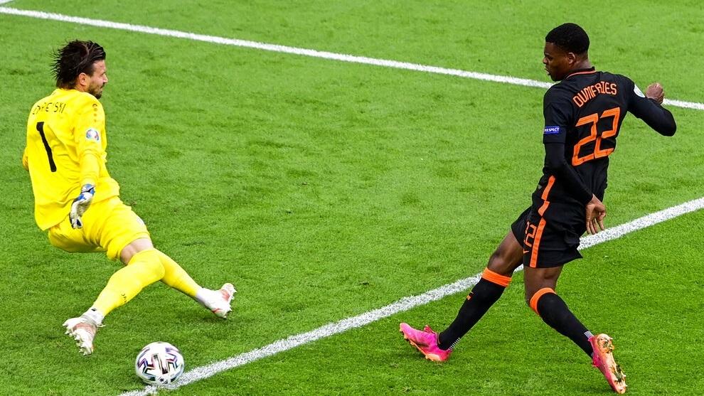 Denzel Dumfries des Pays-Bas, à droite, frappe le ballon à côté du gardien de but de la Macédoine du Nord Stole Dimitrievski.