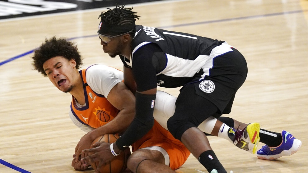 Phoenix Suns forward Cameron Johnson, left, and Los Angeles Clippers guard Reggie Jackson battle for a loose ball.