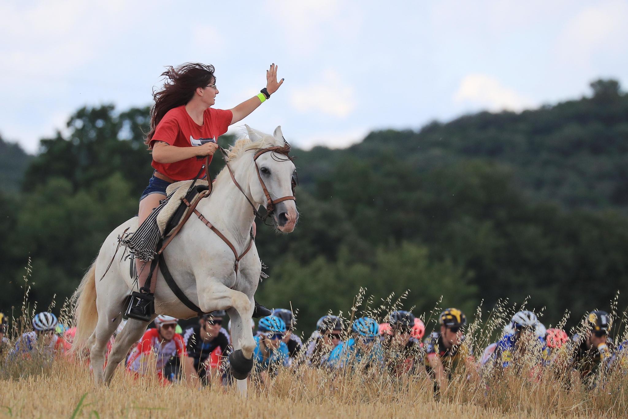 Una mujer saluda al pelotón mientras monta a caballo durante la duodécima etapa del Tour.