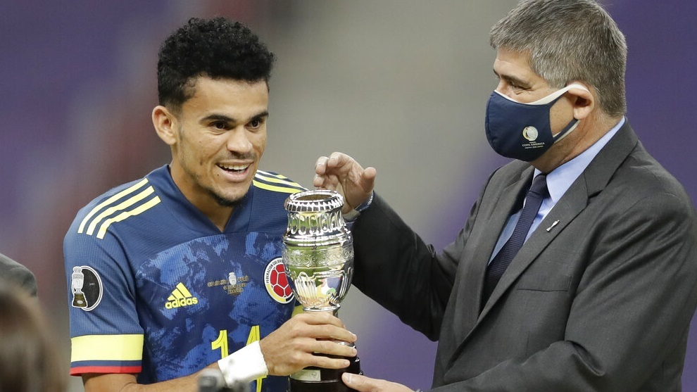 Conmebol General Secretary Jose Astigarraga, gives to Luis Diaz the best player of the match trophy.