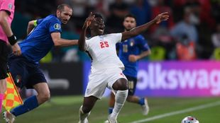 Italy's Giorgio Chiellini tugs the shirt of England's Bukayo...