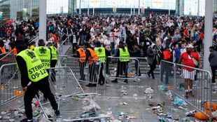 Stewards replace barricades after they were knocked over by supporters...