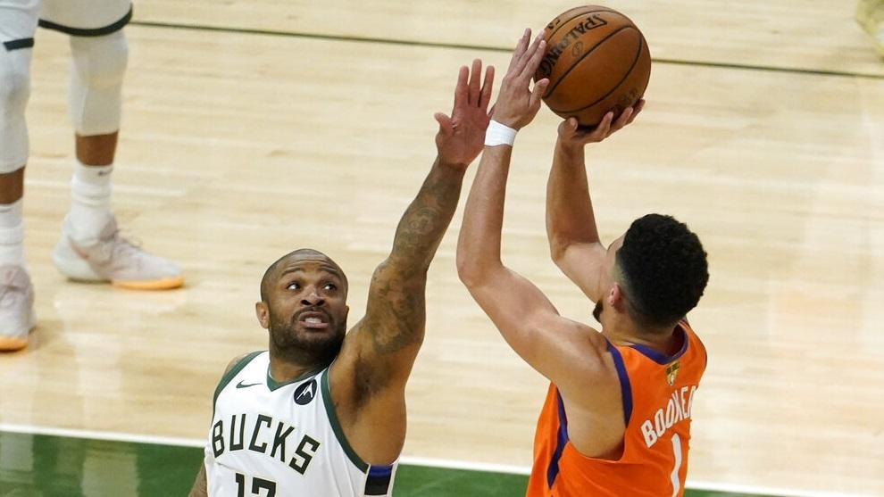 مهاجم Milwaukee Bucks PJ Tucker (17) يحاول صد تسديدة من حارس Phoenix Suns Devin Booker (1).
