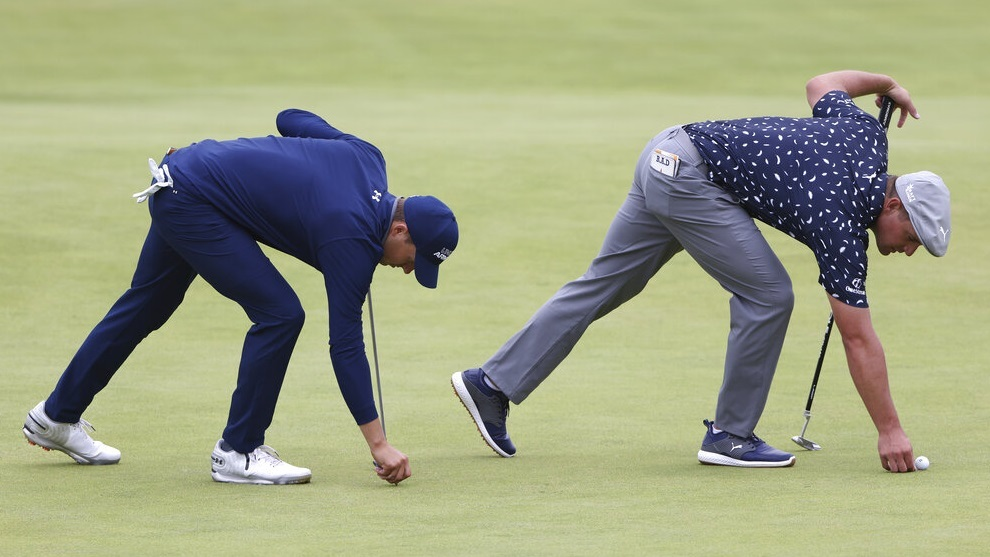 Jordan Spieth (left) and Bryson DeChambeau (right) repair pitch marks on the 18th green.