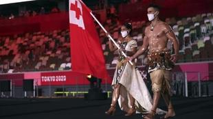 Pita Taufatofua parading in Tokyo as Tonga's flag bearer.