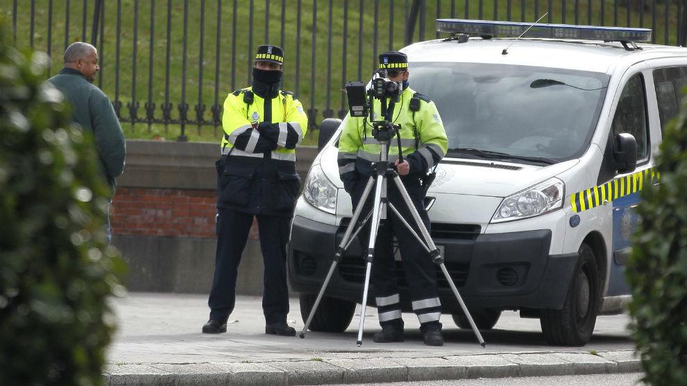 Dos agentes de Movilidad de Madrid instalan un radar de velocidad en El Retiro.