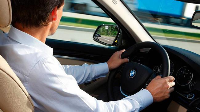 Un conductor mira por el espejo retrovisor de la izquierda.