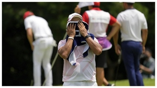 Hideki Matsuyama se seca el sudor, mientras al fondo Xander Schauffele...
