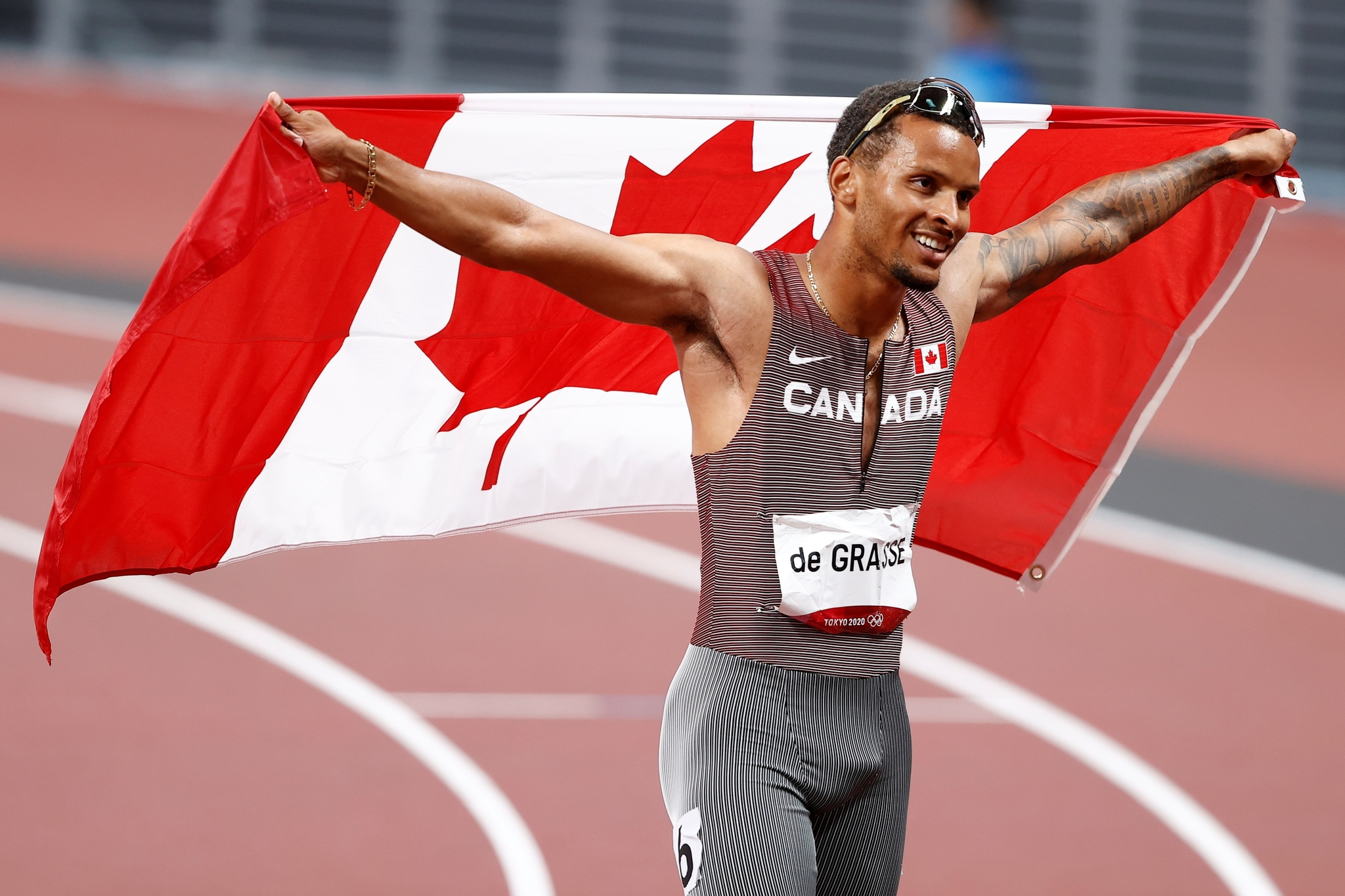 Andre De Grasse celebrates with Canada's flag after winning the men's 200m race.