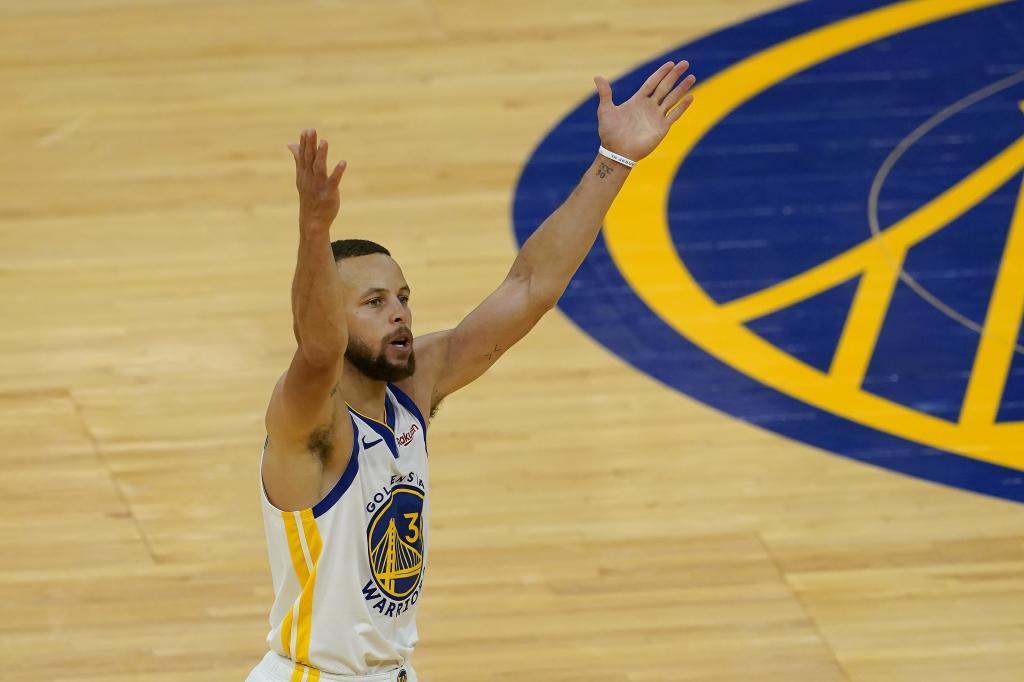 Stephen Curry celebra un triple con los Warriors alzando los brazos.