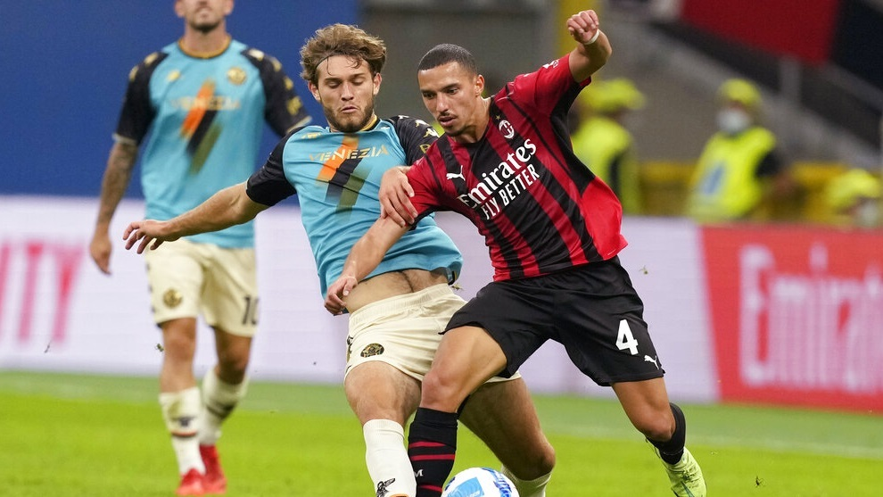 Venezia's Tanner Tessmann, left, challenges for the ball with AC Milan's Ismael Bennacer.