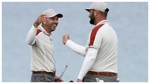 Sergio García y Jon Rahm se felicitan tras el putt de Jon en el hoyo...