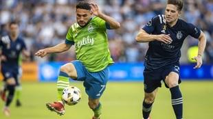 Seattle Sounders midfielder Cristian Roldan attacks the ball past...