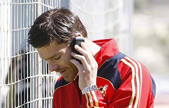 Xabi Alonso habla por tel�fono durante la concentraci�n de la selecci�n en Las Rozas.