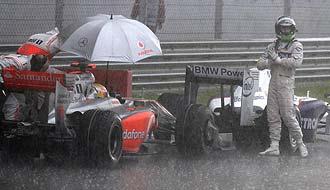 Heidfeld aparece fuera de su BMW bajo el diluvio, mientras Hamilton sigue dentro de su McLaren.