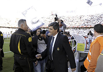 Juande Ramos sale al campo mientras varios 'Juan D�lares' vuelan sobre �l.