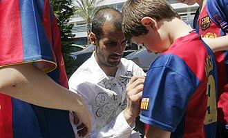 Guardiola firma aut�grafos a unos ni�os con las camisetas del Barcelona.