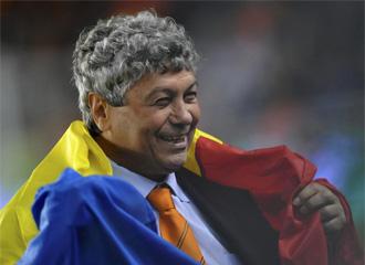 Lucescu celebra el haber ganado la UEFA envuelto en una bandera de Rumanía.