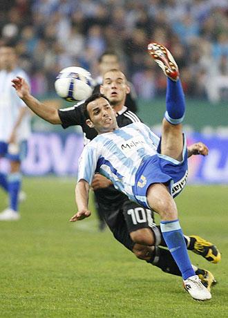 Javi Calleja golpea al balón en presencia de Sneijder en el partido de esta temporada del Málaga ante el Real Madrid en La Rosaleda