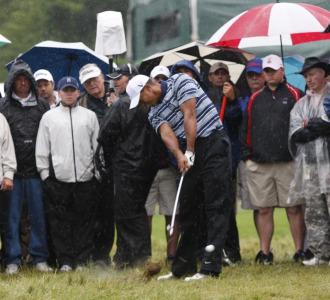 Tiger Woods intenta sacar la bola del 'rough'.