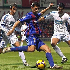 Roberto, del Huesca, ante dos rivales del Xerez.