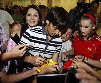 David Silva firma autógrafos a la llegada de la selección a Madrid.