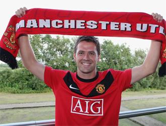 Michael Owen posa con la camiseta y la bufanda del United