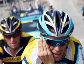 Contador habla por teléfono con Armstrong detrás de él.