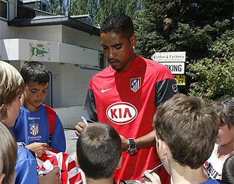 Cléber Santana firma autógrafos a unos niños.