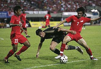 Riera pelea un balón ante un jugador de Singapur