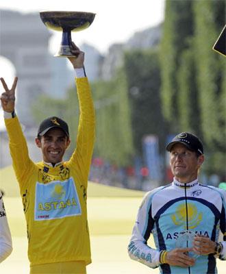 Lance Armstrong mira a Alberto Contador mientras levanta el premio de ganador del Tour de Francia 2009.