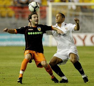 Adriano pelea un bal�n con Mata, del Valencia, en el primer partido del Trofeo Carranza entre el Valencia y el Sevilla