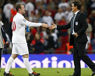 Capello saluda a Rooney durante el partido.