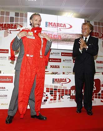 Eduardo Inda sonríe mientras sostiene el mono de piloto regalo de Luca di Montezemolo.