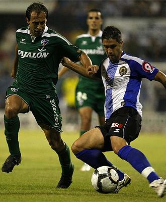 Bautista y Robert pugnan por un balón en el partido entre Hércules y Huesca