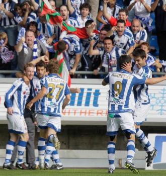 Varios jugadores de la Real celebran un gol junto a aficionados donostiarras en Soria.