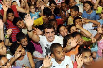 Fernando Alonso, rodeado de niños en la visita como embajador de Unicef a una favela que llevó a cabo antes de la disputa de anterior Gran Premio de Brasil.