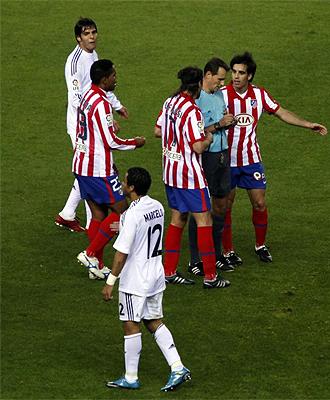 Clos Gómez recibe las protestas de los jugadores del Atlético durante el derbi ante el Madrid