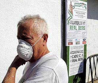 Un empleado del Betis, con la máscara protectora por la epidemia de gripe A, pasa delante del cartel del encuentro que debían haber disputado verdiblancos y Villarreal B el pasado 1 de noviembre