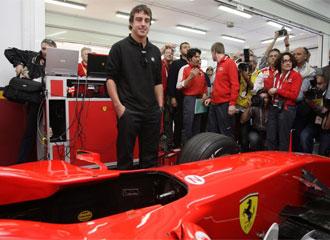Alonso posa para la prensa detrás de un Ferrari
