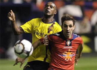 El jugador de Osasuna, Juanfran Torres, pugna por un balón con Eric Abidal