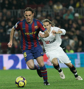 Milito conduce el bal�n durante el partido durante el Sevilla.