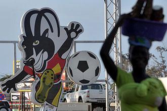 Una vendedora callejera camina cerca de un cartel con la mascota de la Copa de �frica.