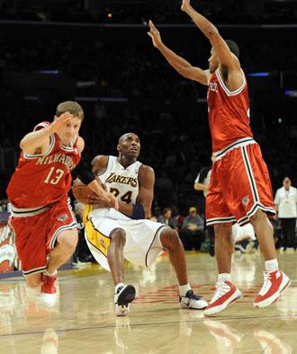 Kobe Bryant cae al suelo ante Luke Ridnour y Charlie Bell