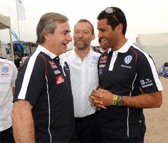 Carlos Sainz habla con Al-Attiyah en presencia de Kris Nissen.