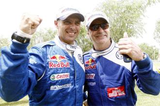 Lucas Cruz y Carlos Sainz con gesto de victoria tras ganar el Dakar 2010.