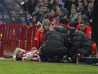 Forl�n es atendido de su esguince-traumatismo durante el partido frente al Sporting.