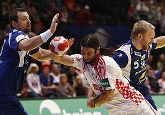 Ivano Balic es parado por dos jugadores islandeses.