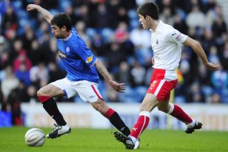 Flynn trata de parar a Novo en el partido entre el Rangers y el Falkirk.