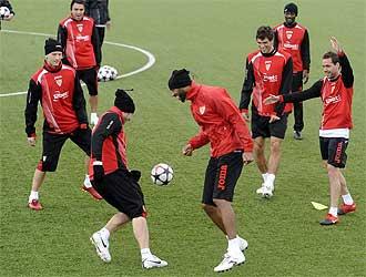 Los jugadores del Sevilla se ejercitan sobre uno de los campos de hierba artificial de la Ciudad Deportiva.